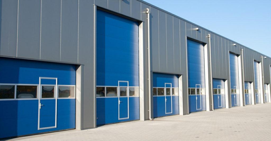 Teollisuuden nosto-ovet käyntiovilla ja ikkunariveillä.