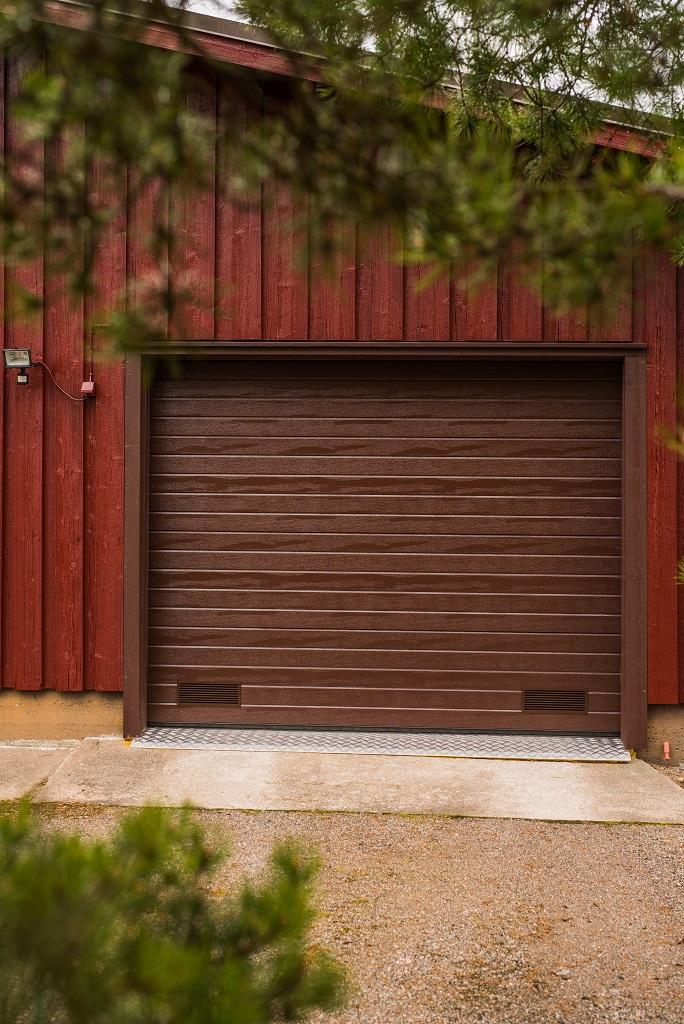 Vaakaurakuvionti antaa ovella klassisen ilmeen. Yksinkertainen panelointia jäljittelevä kuviointi on yhtä rakennuksen kanssa.