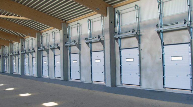 Rivi nosto-ovia pystynostokiskoilla. Erilliset jousipukit oviaukon yläpuolella.