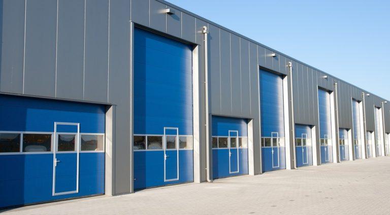 Varastohallin nosto-ovet Fullview-ikkunariveillä ja käyntiovilla. Ikkunoiden ja käyntiovien karmit saatavilla myös oven värissä. Lamellimalli: Macrorib.