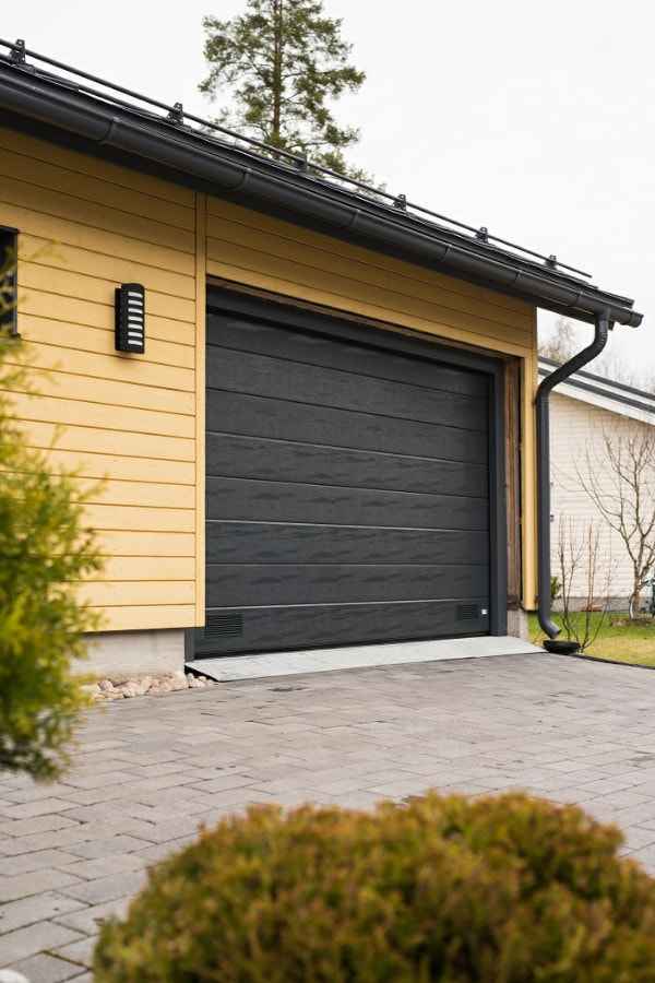 Harmaa nosto-ovi leveällä vaakauralla Kouvolassa. Autotallin ovi varustettiin sähköisellä ovenavaajalla. Automatisoitu ovi avautuu helposti nappia painamalla, eikä esimerkiksi autosta tarvitse nousta talliin ajettaessa.