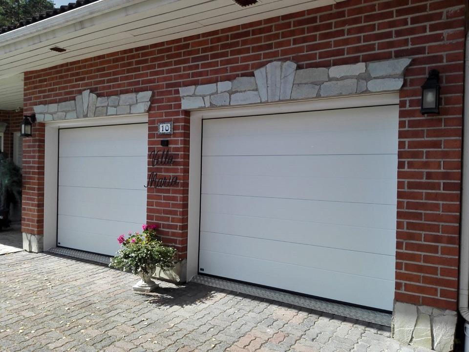 Autotallin nosto-ovet Hollolassa. Purkamalla vanhat pariovet oviaukoista karmeineen ja asentamalla uudet nosto-ovet seinän sisäpintaan, saatiin aukkoon lisää leveyttä noin 20 senttiä.