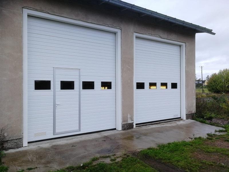 Teollisuuden nosto-ovet Lapinjärvellä. Vanhojen pariovien tilalle uudet nosto-ovet tummennetuilla ikkunoilla. Toiseen oveen käyntiovi ja viimeistelynä valkoiset pielityöt puusta.