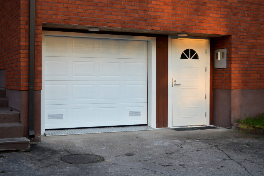 Autotallin nosto-ovi peilikuviolla sekä Kaskipuun ulko-ovi vastaavalla kuosilla Kotkassa