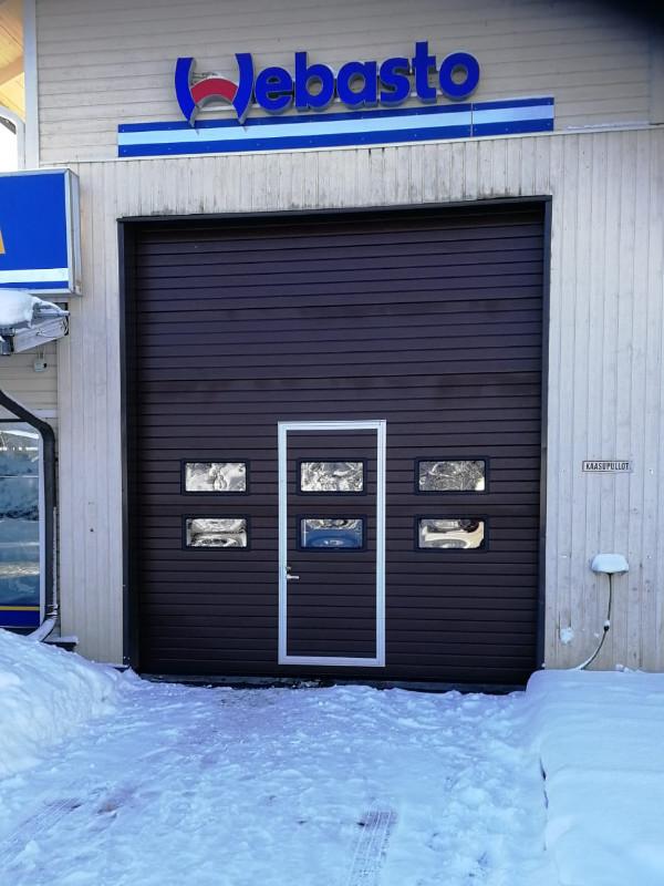 Pesuhallin nosto-ovi Elimäellä ikkunoilla, käyntiovella ja oviautomatiikalla
