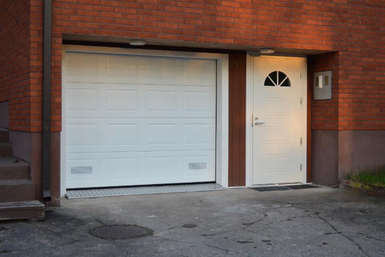 Uusi autotallin nosto-ovi sekä rakennuksen pääovi syksyisessä valossa
